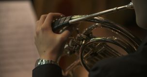 Musician playing French horn during concert. Lockdown shot of musician playing French horn. Male is using brass instrument during a concert. He is wearing tuxedo stock video footage