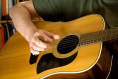 Musician playing guitar. Arm and hand of person strumming acoustic guitar Stock Photos