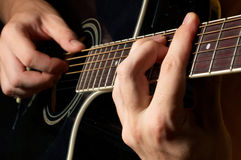 Musician playing guitar. Musician playing on black acoustic guitar Stock Photo