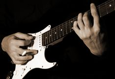 Musician playing guitar. Musician playing on black  guitar Stock Image