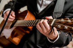 Musician playing a guitar. Close-up photo Royalty Free Stock Image