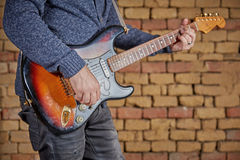 Musician playing guitar in front of brick wall Stock Photo