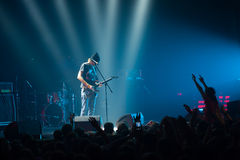 Musician playing guitar in front of a crowd of people at a concert at the club. Stock Photos