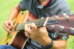 Musician playing guitar in the park. Musician playing acoustic guitar in the park royalty free stock photos