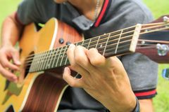 Musician playing guitar in the park. Musician playing acoustic guitar in the park stock photography
