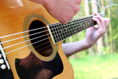 (Musician playing a guitar. Musician playing a six-string guitar at a picnic Royalty Free Stock Photo