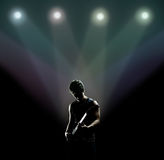Musician playing the guitar on the stage. Young musician playing the guitar on the stage royalty free stock photos