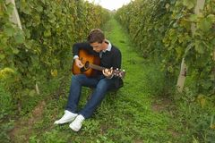 Musician playing guitar. Young musician playing classic guitar in vineyard stock image