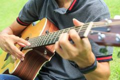 Musician playing Hamonic picking technic on acoustic guitar. In the park royalty free stock image