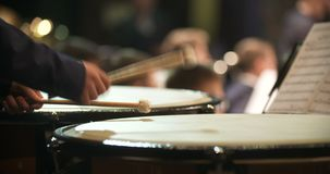 Musician playing kettledrum. Close-up shot of musician playing kettledrum. Male artist performing in music concert. He is hitting sticks on percussion instrument stock video footage
