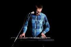 Musician playing on keyboard electric piano and singing on dark. Musician concept.  Royalty Free Stock Photo