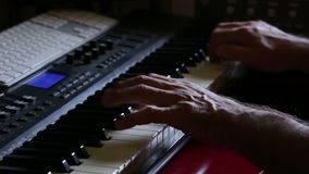 Musician playing on the keyboard synthesizer piano keys. Musician plays a musical instrument. Male hands playing electric piano, close-up. Musician in a suit stock video