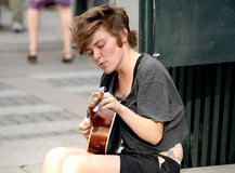 Musician playing for money on a street Stock Image