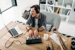 Musician playing on MPC pad. Handsome musician playing on MPC pad and looking at laptop royalty free stock images