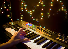 Musician playing on musical keyboard. (Close up of a hand playing a MIDI controller keyboard in black background Royalty Free Stock Image