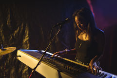 Musician playing piano in illuminated nightclub. Female musician playing piano in illuminated nightclub Stock Images