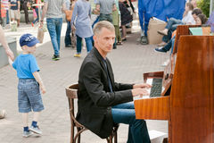 Musician playing on piano outdoor and walking families Royalty Free Stock Photo