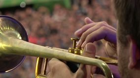 A musician playing on a pipe in front of thousands of people