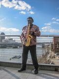 Musician playing sax on banks of the River Thames. London / England / UK - 02/19/2013: View at the male musician playing sax on bridge, banks of the River Thames royalty free stock photo
