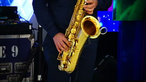 Musician is playing on saxophone in concert. Close-up on fingers pressing the keys of the instrument stock video footage
