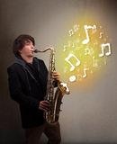 Musician playing on saxophone with musical notes. Handsome young musician playing on saxophone with musical notes Stock Photography