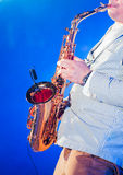 Musician playing saxophone on stage Stock Image