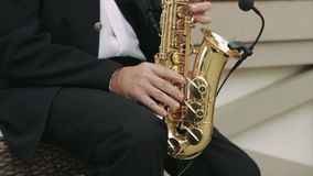 Musician Playing The Saxophone in The Street. Close-Up on Fingers Pressing the Keys of the Instrument. Musician Playing the Saxophone in the Street. the Camera stock footage