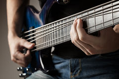 Musician playing on six-string bass guitar Stock Photo