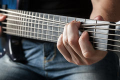 Musician playing on six-string bass guitar Stock Photography