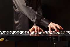 Musician playing the synth on black background Stock Photography