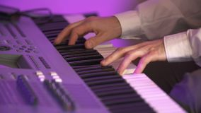 Musician playing synthesizer. Close up shoot of Musician playing synthesizer oat concert live event. Music live event background. Musician playing synth stock video footage
