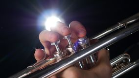 Musician playing trumpet on a black background with a spotlight. Seen in frame musicians hands and fingers with manicure click on a tool button, metal parts of stock footage
