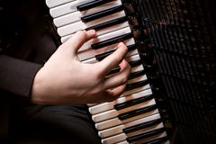 Musician plays the accordion against a dark background Royalty Free Stock Photos