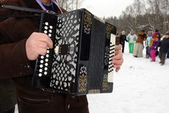 The musician plays accordion on the feast of Maslenitsa. The musician plays accordion in winter weather on the feast of Maslenitsa stock photography