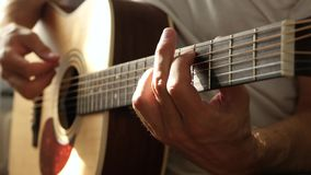 The musician plays an acoustic guitar, pressing the fingers of the string close-up. Man resting singing a song. 4K stock video footage