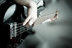 The musician plays on a black, shiny bass guitar. The musician plays on a black shiny bass guitar on a blurred background Stock Images