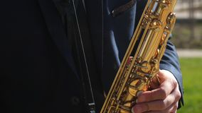 The musician plays the blues wind instrument. man playing saxophone jazz music. Saxophonist in dinner jacket play on. Musician plays the blues wind instrument stock footage