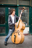 Musician plays contrabass. Musician sings and plays contrabass in Portobello market, London, United Kingdom royalty free stock photography
