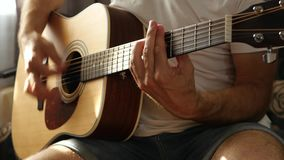 The musician plays a fast rhythm on a yellow acoustic guitar close-up, a ray of light falls on the fingers and neck of. The guitar. The concept of music and stock footage