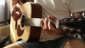 The musician plays a fast rhythm on a yellow acoustic guitar. The concept of music and creativity.