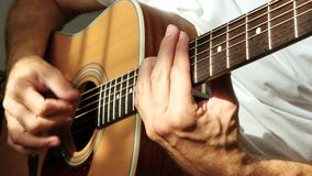 The musician plays a fast rhythm on a yellow acoustic guitar, holding the strings on the bar. Guitarist`s fingers close up. 4k stock video