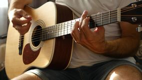 The musician plays a fast rhythm on a yellow acoustic guitar, a ray of light falls on the fingers and neck of the guitar. The concept of music and creativity stock video footage