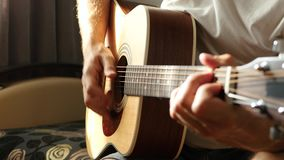 The musician plays a fast rhythm on a yellow acoustic guitar. The sun`s rays pass through the fingers and strings. Close up stock video