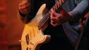 Musician plays guitar at a concert in a jazz bar. Close up stock footage
