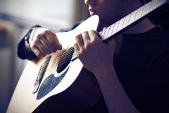A musician plays his acoustic guitar, holding the fretboard at the base royalty free stock photography