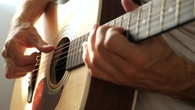 The musician plays his fingers on a yellow acoustic guitar. Guitarist`s fingers close up. 4k stock video