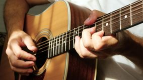 The musician plays with his fingers on a yellow acoustic guitar, a ray of light falls on the fingers and neck of the. Guitar. The concept of music and stock footage