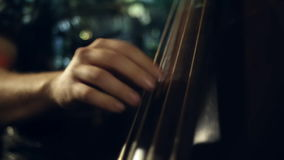 The musician plays jazz music on the cello. In the club stock video footage