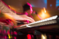Musician plays keyboards in a rock band.  Stock Photography