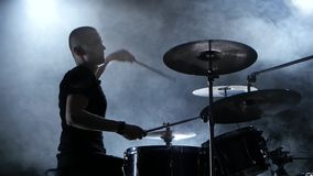 Musician plays a melody on the drums. Black smoke background. Side view. Silhouettes stock footage
